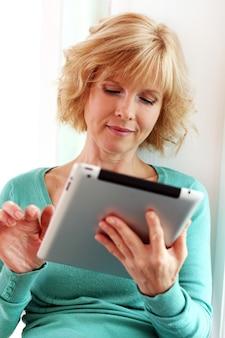 Mujer de mediana edad relajante con tableta comper