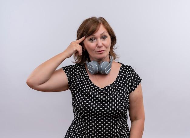 Mujer de mediana edad seriamente mirando poniendo su dedo en la sien con auriculares alrededor de su cuello en la pared blanca aislada