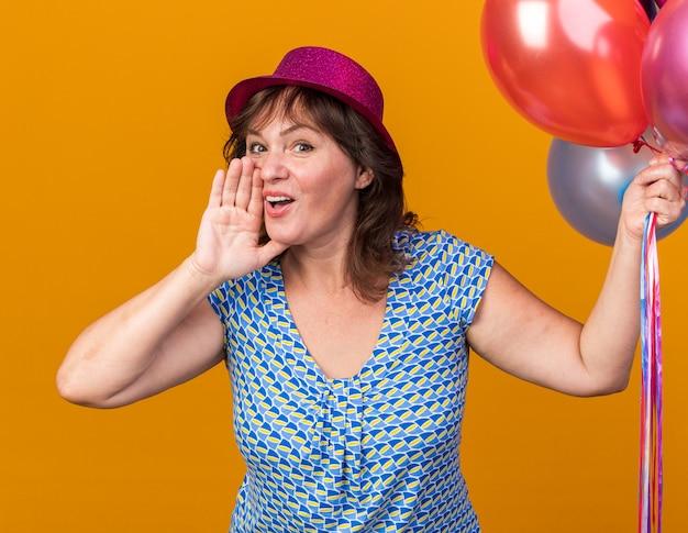 Mujer de mediana edad con sombrero de fiesta sosteniendo globos de colores gritando con la mano cerca de la boca feliz y alegre celebrando la fiesta de cumpleaños de pie sobre la pared naranja