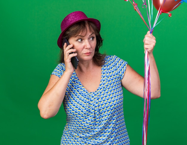 Mujer de mediana edad con sombrero de fiesta sosteniendo globos de colores mirando confundido mientras habla por teléfono móvil celebrando la fiesta de cumpleaños de pie sobre la pared verde