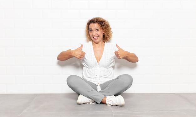 Mujer de mediana edad sonriendo ampliamente luciendo feliz, positiva, segura y exitosa, con ambos pulgares hacia arriba