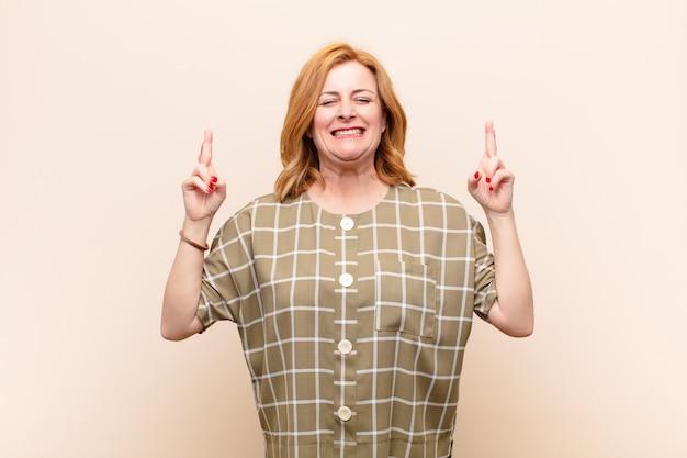 Mujer de mediana edad sonriendo y cruzando ansiosamente ambos dedos, sintiéndose preocupada y deseando o esperando buena suerte