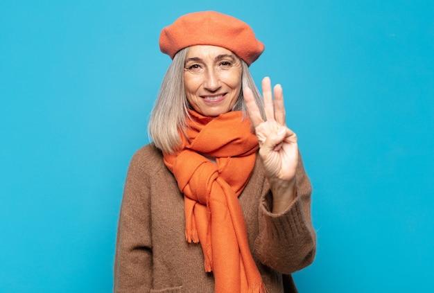 Mujer de mediana edad sonriendo y mirando amistosamente, mostrando el número tres o tercero con la mano hacia adelante, contando hacia atrás