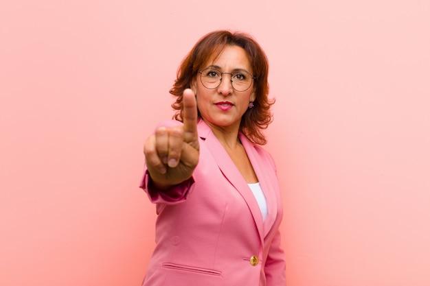 Mujer de mediana edad sonriendo con orgullo y confianza haciendo la pose número uno triunfante, sintiéndose como una pared rosa líder