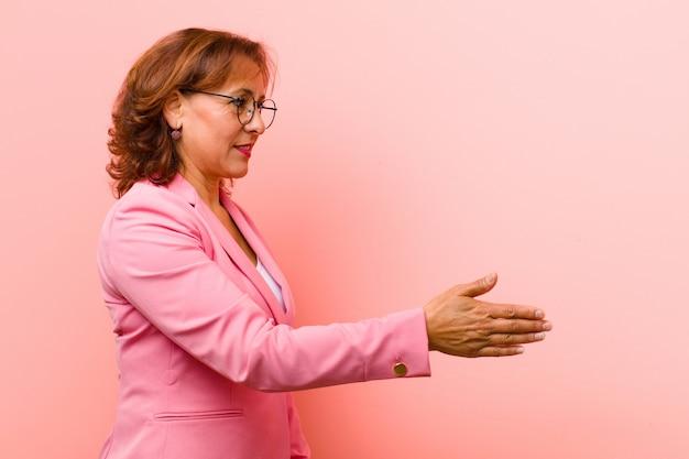 Mujer de mediana edad sonriendo, saludando y ofreciendo un apretón de manos para cerrar un acuerdo exitoso, concepto de cooperación contra la pared rosa