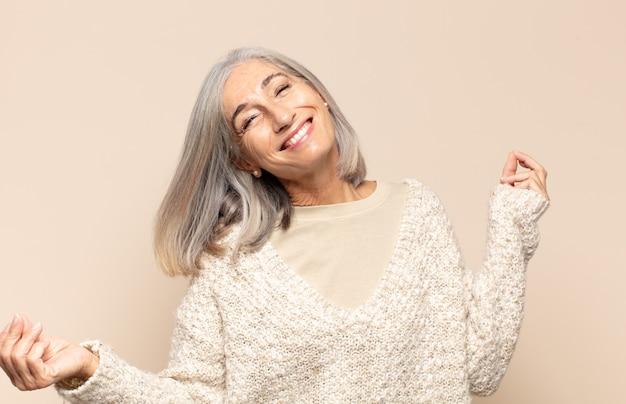 Mujer de mediana edad sonriendo, sintiéndose despreocupada, relajada y feliz, bailando y escuchando música, divirtiéndose en una fiesta