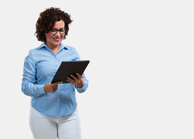 Mujer de mediana edad, sonriente y confiada, sosteniendo una tableta, usándola para navegar por internet