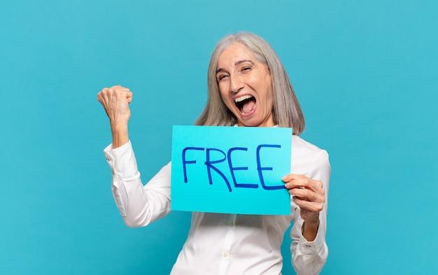Mujer de mediana edad sosteniendo la hoja de papel con la palabra gratis