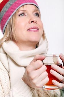 Mujer de mediana edad con té caliente vistiendo ropa de invierno sobre un fondo blanco.