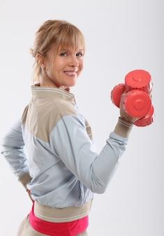 Mujer de mediana edad trabajando con pesas rojas