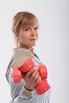 Mujer de mediana edad trabajando con pesas