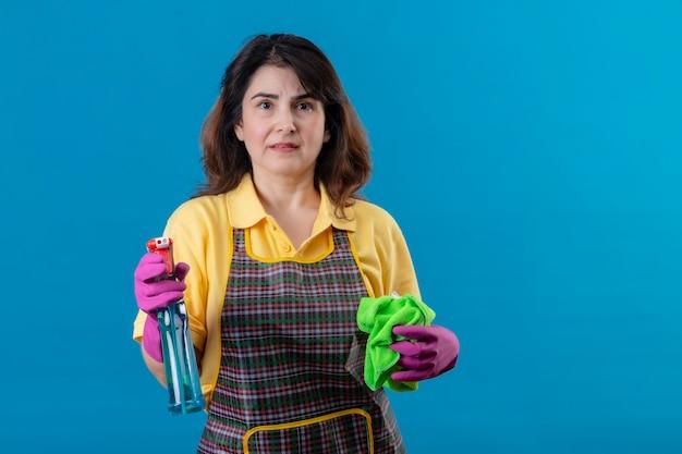 Mujer de mediana edad vistiendo delantal y guantes de goma sosteniendo alfombra y spary de limpieza