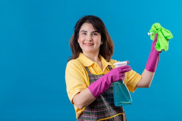 Mujer de mediana edad vistiendo delantal y guantes de goma sosteniendo spary de limpieza y alfombra sonriendo con cara feliz de pie sobre la pared azul