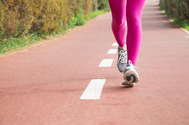 Mujer con medias rosas y zapatillas grises.