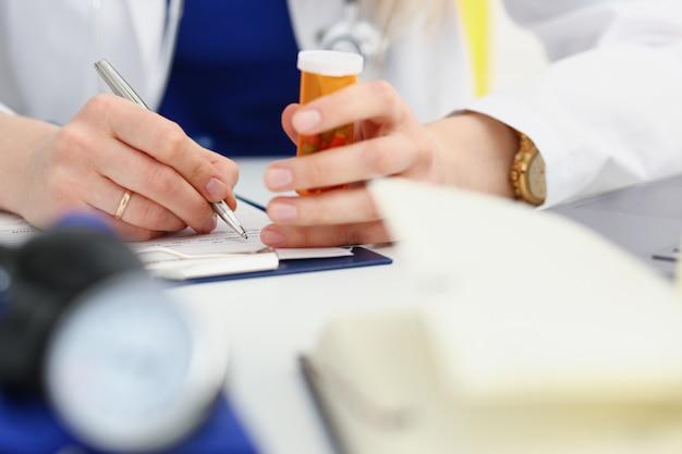 Mujer medicina doctor mano sostenga el tarro de píldoras y escriba la receta al paciente en la mesa de trabajo. panacea y salvavidas, tratamiento de prescripción, concepto de farmacia legal. formulario vacío listo para ser usado