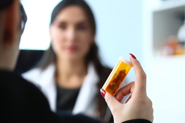 Mujer medicina doctor mano tarro de pastillas