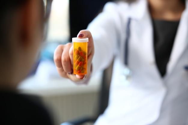 Mujer medicina doctor mano tarro de píldoras y