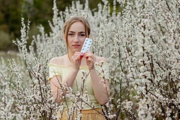 Mujer con medicina en las manos luchando contra las alergias de primavera al aire libre