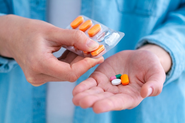Mujer de medicina tomando pastillas y vitaminas para el bienestar en el hogar.