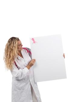 Mujer médico con estetoscopio rosa con cáncer de mama cinta rosa con tarjeta en blanco sobre un fondo blanco.