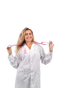 Mujer médico con estetoscopio rosa con cinta rosa de cáncer de mama sobre un fondo blanco.