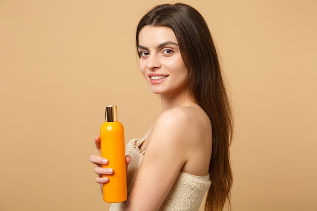 Mujer medio desnuda morena de cerca con una piel perfecta, maquillaje desnudo aislado en la pared de color beige pastel