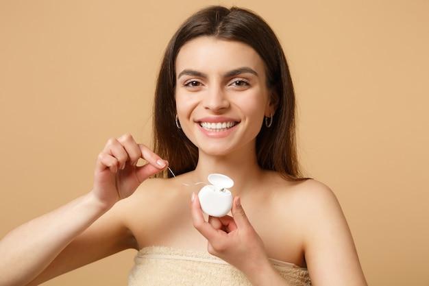 Mujer medio desnuda morena de cerca con una piel perfecta, maquillaje desnudo con hilo dental aislado en la pared de color beige pastel
