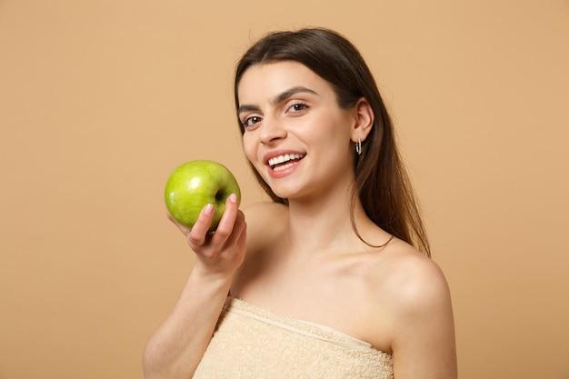 Mujer medio desnuda morena de cerca con una piel perfecta, maquillaje desnudo sostiene manzana aislada en la pared de color beige pastel