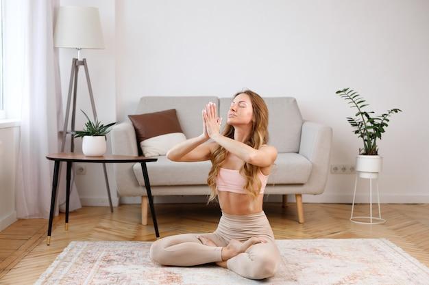 Mujer medita en casa en la sala de estar