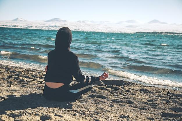 Mujer medita en posición de loto en la playa sentada