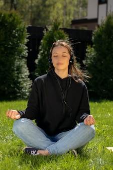 La mujer medita sentada sobre la hierba verde en el césped y escucha música relajante. descansar en el concepto de césped. relajarse en la hierba verde. recreación al aire libre. vacaciones en el pueblo. cálido día soleado de verano.