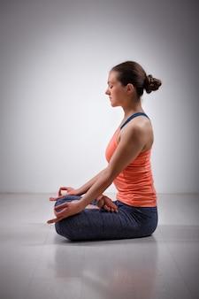 Mujer medita en yoga asana padmasana lotus pose