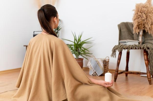 Mujer meditando con bandeja con velas