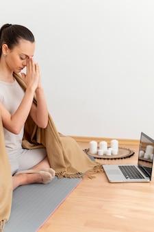Mujer meditando en casa con un portátil al lado