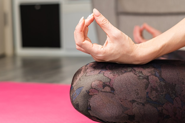 Mujer meditando en casa en el primer plano de la posición de loto. relajación y meditación