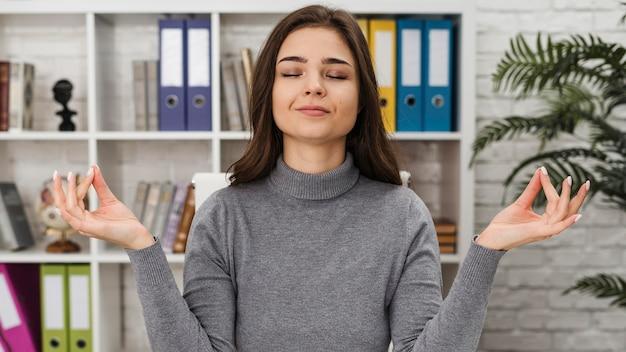 Mujer meditando mientras trabaja desde casa