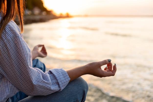 Mujer meditando en la playa con espacio de copia
