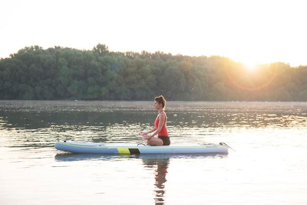 Mujer meditando y practicando yoga durante el amanecer en paddle board