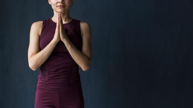 Mujer meditando tomados de la mano en pose de gratitud de yoga namaste