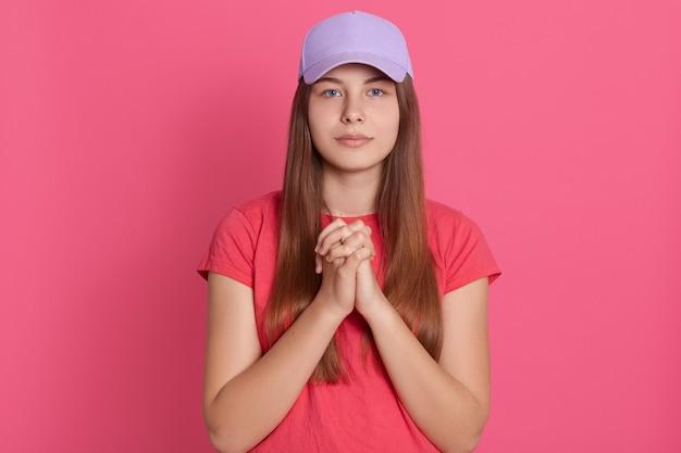 Mujer meditando uniendo sus dos palmas, mira a la cámara, vistiendo camiseta casual y gorra de béisbol