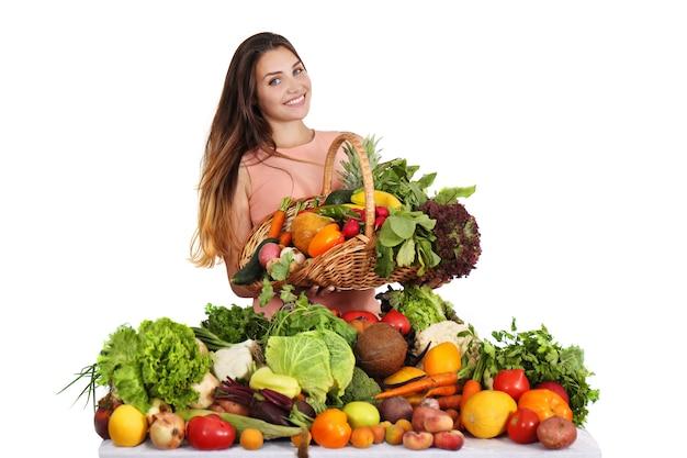 Mujer en la mesa con frutas y verduras.