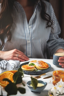 Mujer en la mesa con un hermoso y sabroso desayuno. tortitas de requesón en un plato, taza con café y naranjas sobre un fondo blanco de madera.