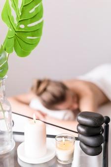 Mujer en mesa de masaje con vela