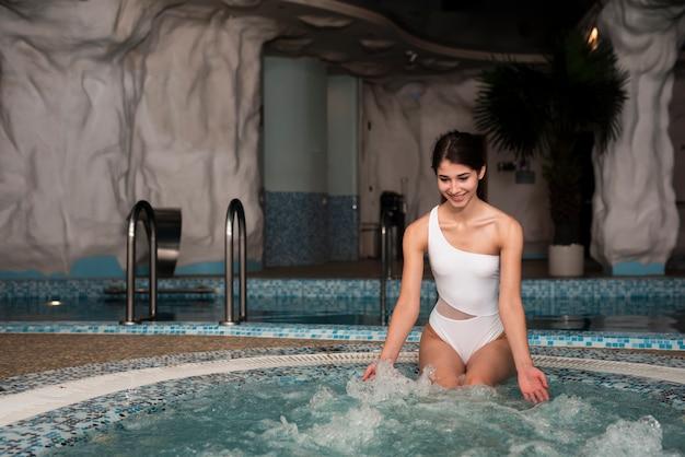 Mujer metiéndose en la bañera de hidromasaje en el spa