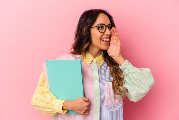 Mujer mexicana joven estudiante aislada sobre fondo rosa gritando y sosteniendo la palma cerca de la boca abierta.