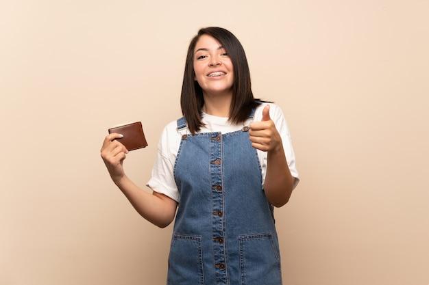 Mujer mexicana joven sobre el fondo aislado que sostiene una cartera