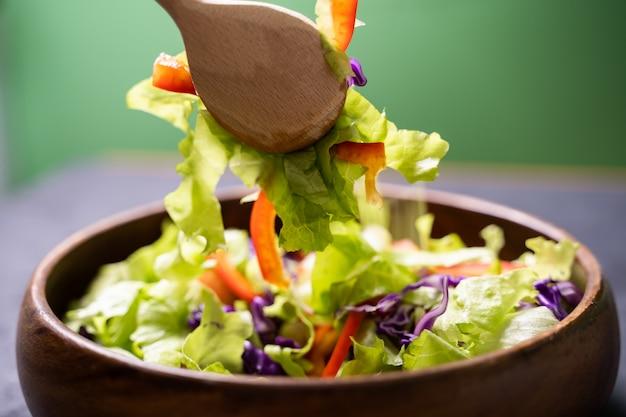 Mujer mezcla deliciosos ingredientes de ensalada superalimento con cucharas de madera en la cocina