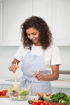 Mujer mezclando una ensalada con cuchara de madera