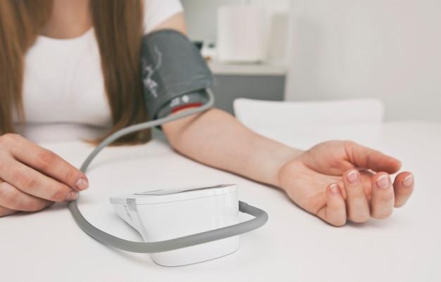 Mujer mide la presión arterial en casa