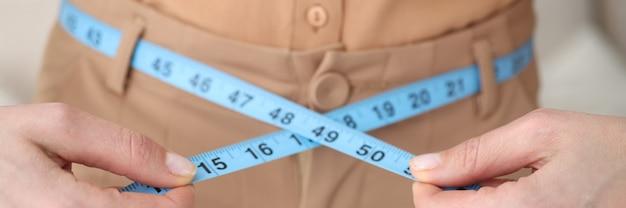 Mujer mide su cintura con primer centímetro